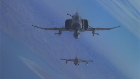 day Air to Air Tight F 4E Phantom II fighter jet, followed being chased MiG 23 F 21 Kfir, over desert terrain warfare, dogfight playback