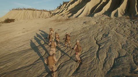 Flying over Group of Running Soldiers in Desert Environment. Shot on Phantom 4K UHD Camera.