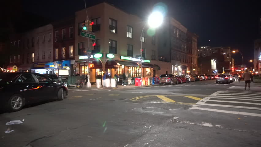 NX establishing shot of NYC queens corner bar at night. Busy urban intersection, out of focus signage. (New York City - October 2016)