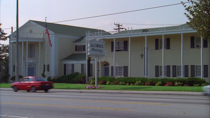 day hold across McCormick Mortuary funeral home yellow colonial style wood building, US flag then push in, raked R