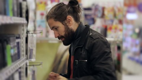Portrait of men with beard and long hair selecting a body spray in supermarket.