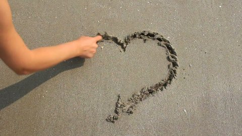 Drawing the heart on the wet sand.