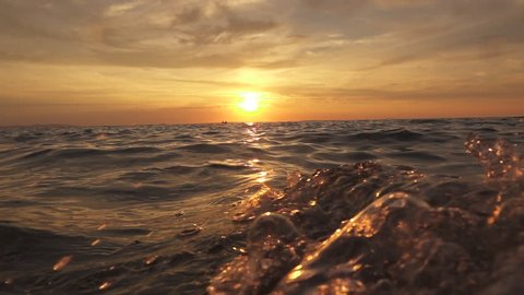 SLOW MOTION, CLOSE UP: Small sailing boat with lovers swinging on rippling sea at magical golden sunset on dreamy tropical island. Big powerful waves swashing to each other and splashing waterdrops
