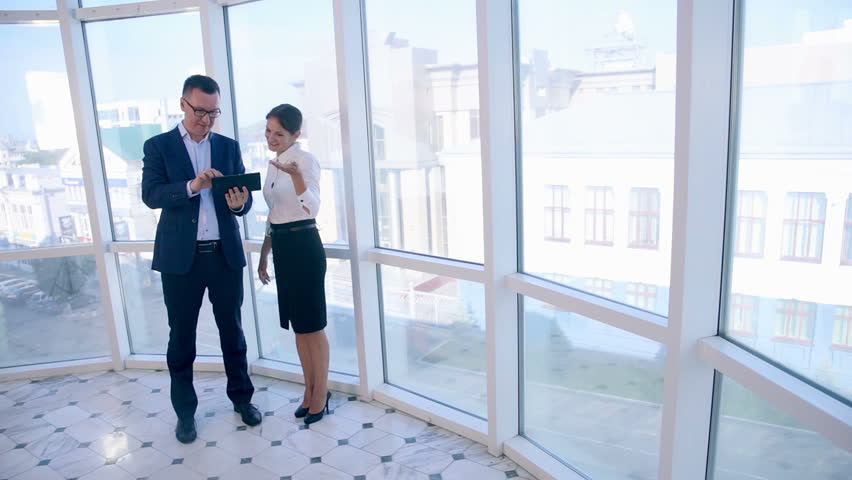 Business, architecture and office concept. Two successful businessmen discuss project on tablet in clean bright office near panoramic window. | Shutterstock HD Video #20935456