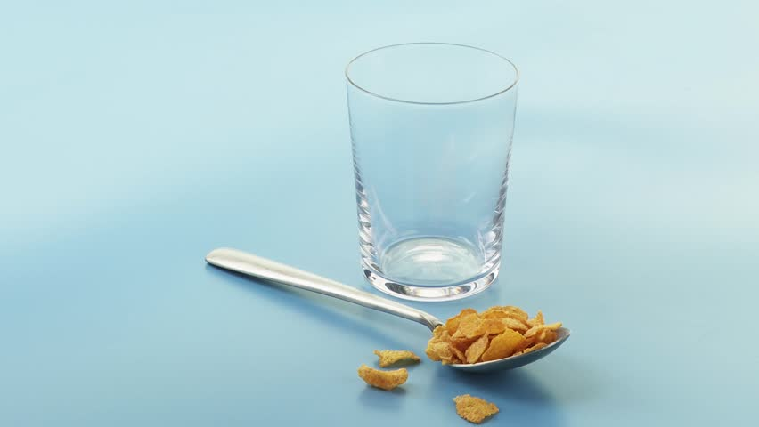 A spoonful of cornflakes and a glass of milk being poured