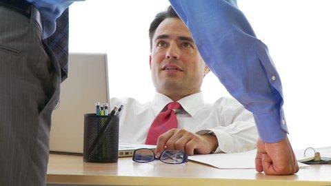 Businessman cowering under irate boss