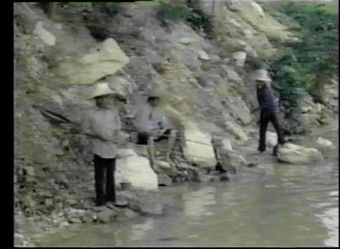 Asian fishermen casting a net in river