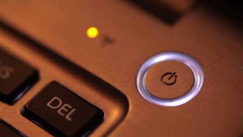 Close up panning footage of a laptop power button.