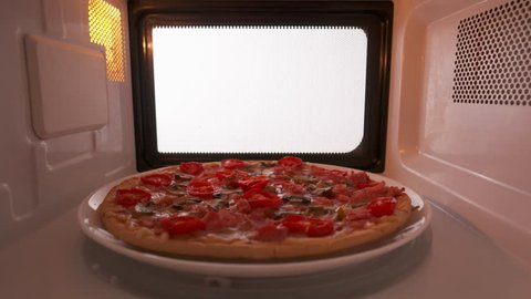 Reheating baked mushroom ham pizza topped with tomato in the microwave oven. Version without external lighting for more natural look.