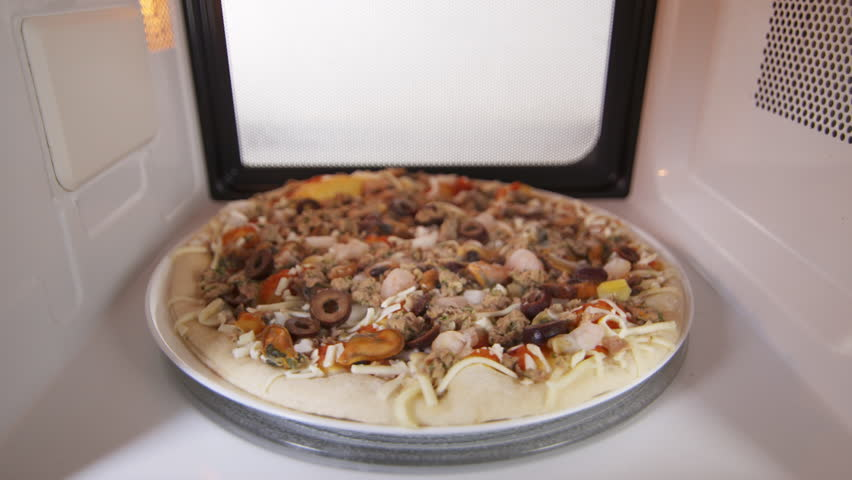 Frozen seafood pizza Frutti di Mare in microwave oven. Mussels, shrimp, clams, calamari, olives, tuna pizza topping. Inside view version with external lighting.