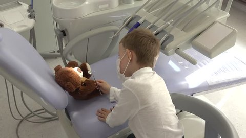 Amusing little child playing the dentist doctor consulting hist teddy bear toy