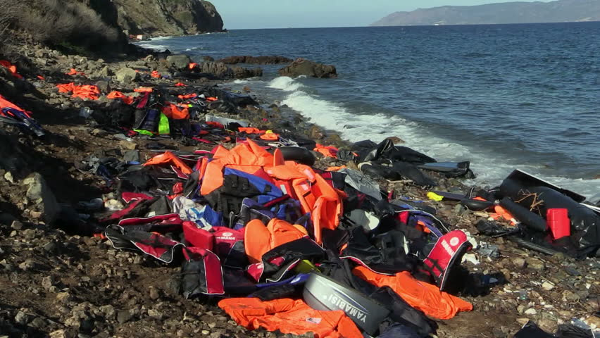 LESVOS, GREECE - NOV 2, 2015: Abandoned by the refugees belongings and life jackets on the rocky shore.
