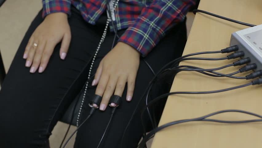 Close up A man shoots a female hands on the sensors lie detector test
