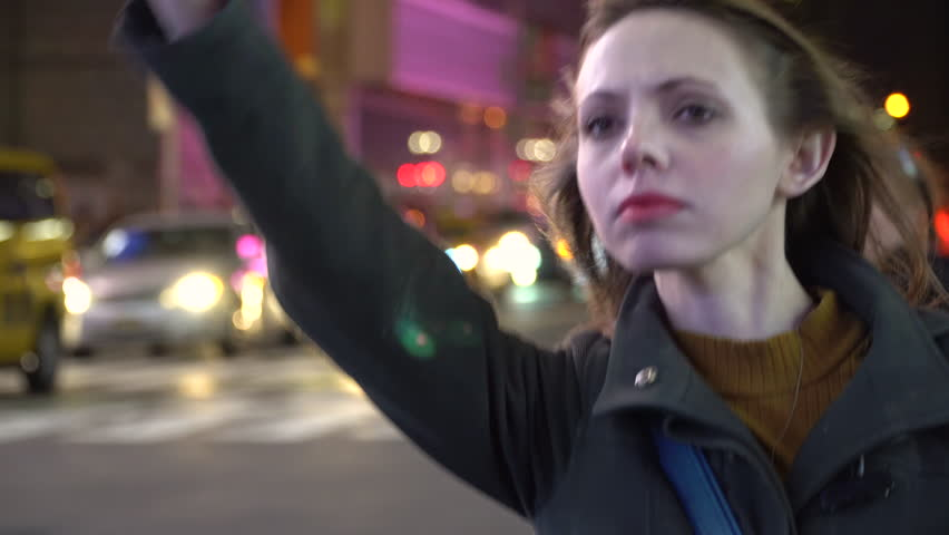 Young female business woman hailing taxi cab in New York City at night. Hipster style startup company executive. Attractive smile as tourists walk by in crosswalk bokeh background, downtown Manhattan. | Shutterstock HD Video #21103402