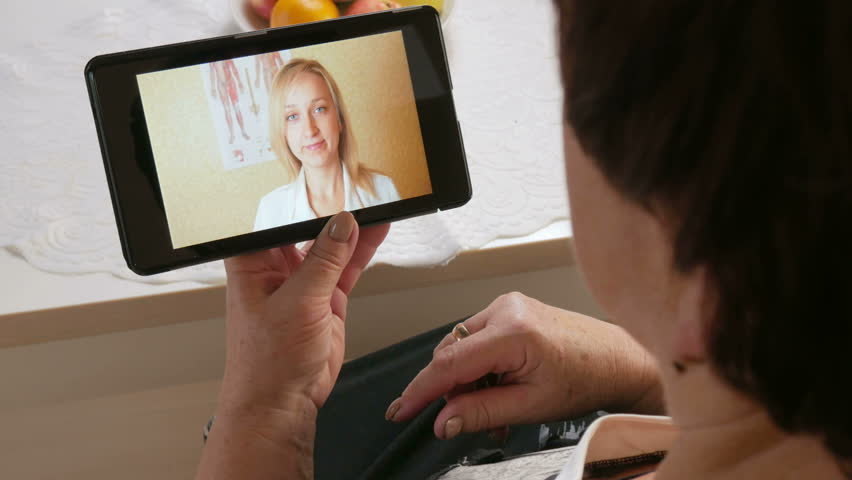 Senior woman coughing and communicate with a doctor on a video conference. Doctor on a tablet online makes recommendations to the patient at home