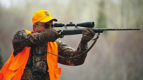 Elk Hunting in a Colorado wilderness during October snowstorm. Hunter raises rifle and looks through rifle scope.