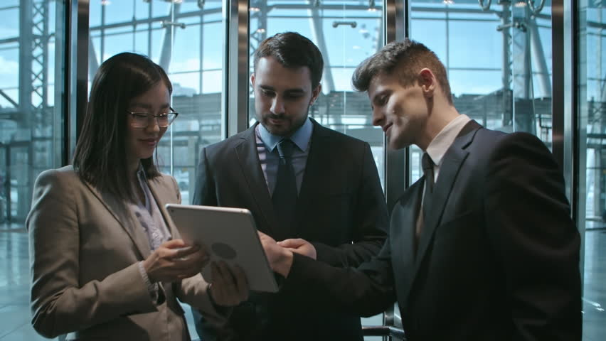 Group of two young Caucasian businessmen and young Asian businesswoman in formalwear using digital tablet and discussing their project in office building elevator