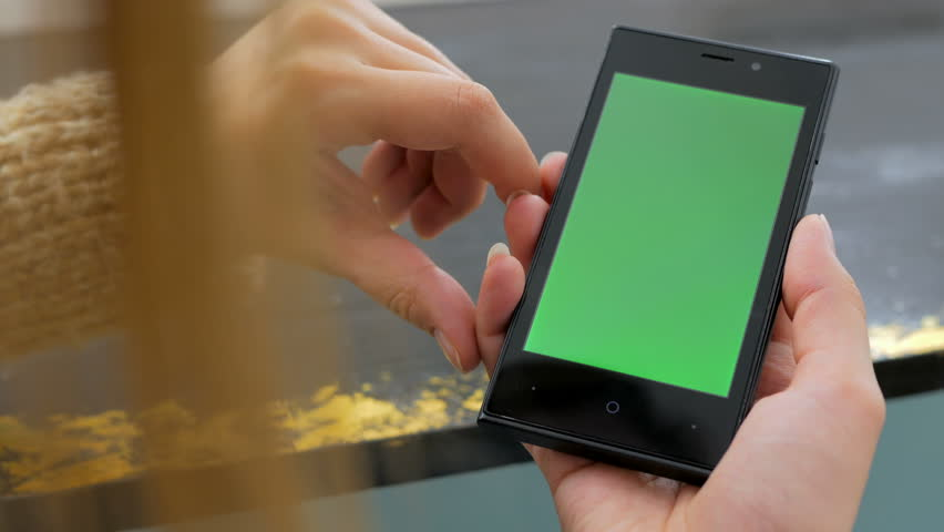 Woman using vertical smartphone with green screen. Close up shot of woman's hands with mobile Close up shot of woman's hands with mobile