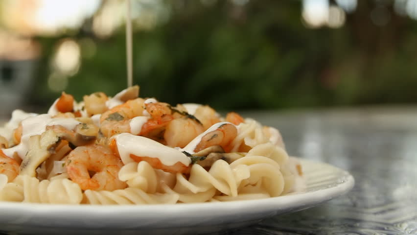 Fusilli Shrimp Pasta With Cream (HD). Fusilli pasta with shrimp and cream being applied on top. Slow panning to the left.