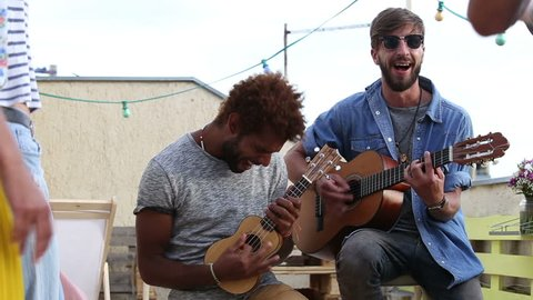 Handsome musicians playing guitar and ukulele and singing on the rooftop terrace on sunny day, friends dancing