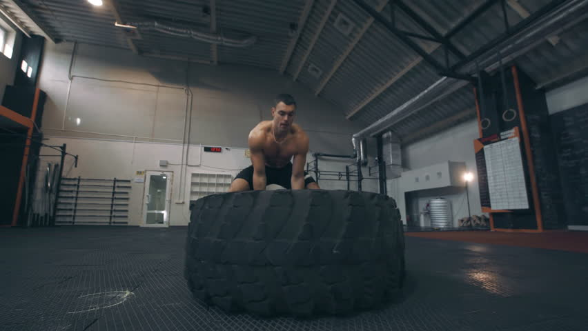 Fit muscular man doing crossfit exercises working out lifting a large rubber tyre in a gym, low angle view in a healthy lifestyle and fitness concept | Shutterstock HD Video #21189862