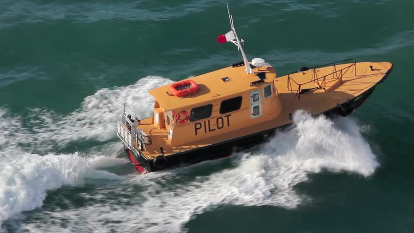 Birds eye view of a yellow pilot boat steaming through the turquoise Caribbean waters.