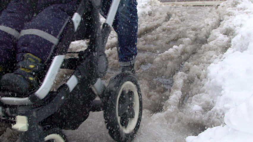 A dad pushing a stroller in slushy snow on a wintry day. Slow motion clip.