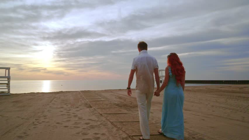 Love couple walking sea beach at sunrise. People holding hands on sea beach. Couple walking on sand beach. Couple in love on vacation. Relationship concept