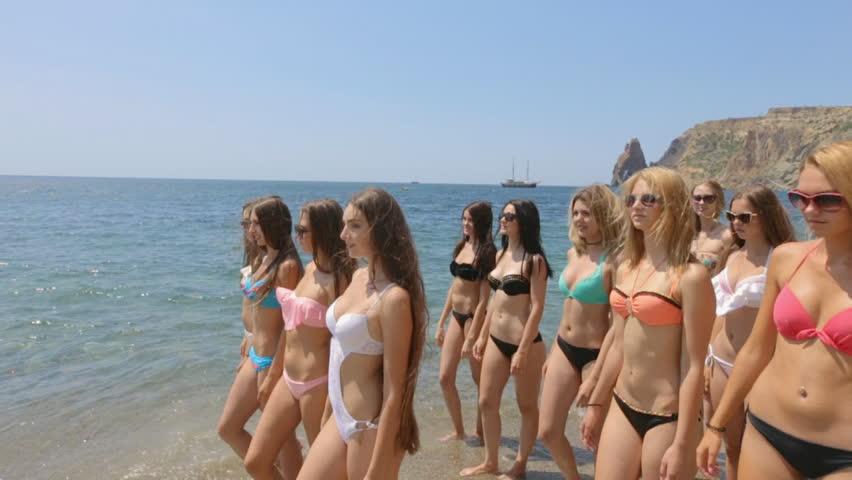 Group of beautiful models in bikinis running along the shore of a beach | Shutterstock HD Video #21199432