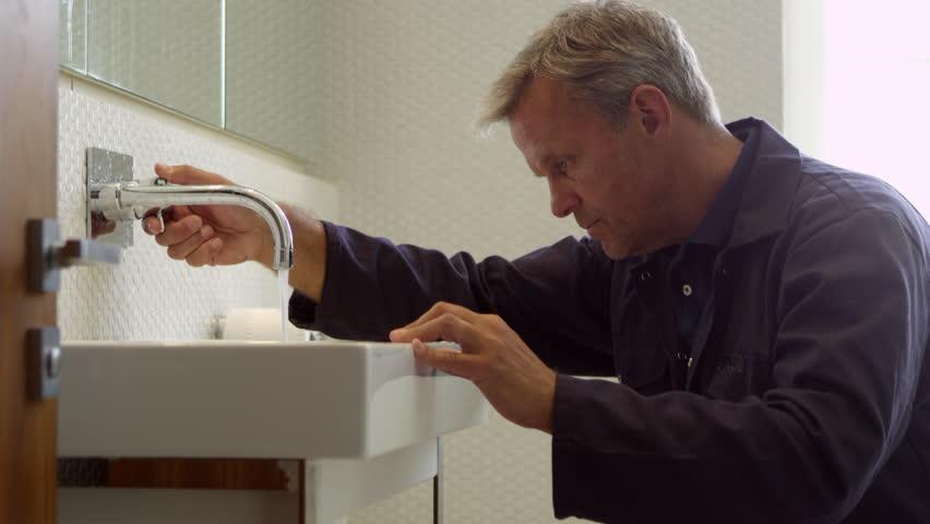 Plumber Working On Sink In Bathroom Shot On R3D