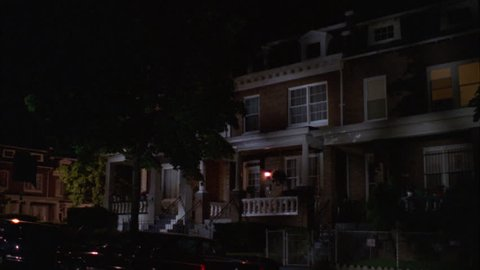 night Wide Raked right two story red brick attached row house white trim steps up porch 1st floor window, light