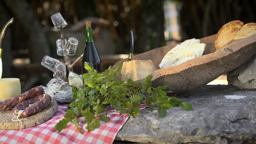 Cheese, ham, salami and wine, traditional food from Sardinia, Italy. Dolly shot. Sequence