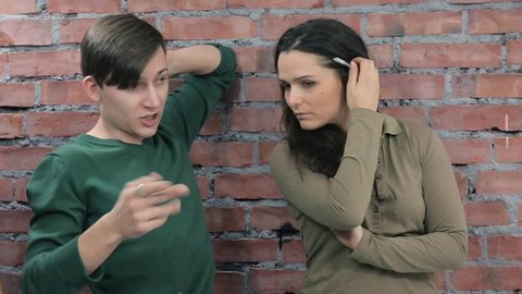 Two men and woman shoot someone on camera. Process. Censure. Brick wall on background.