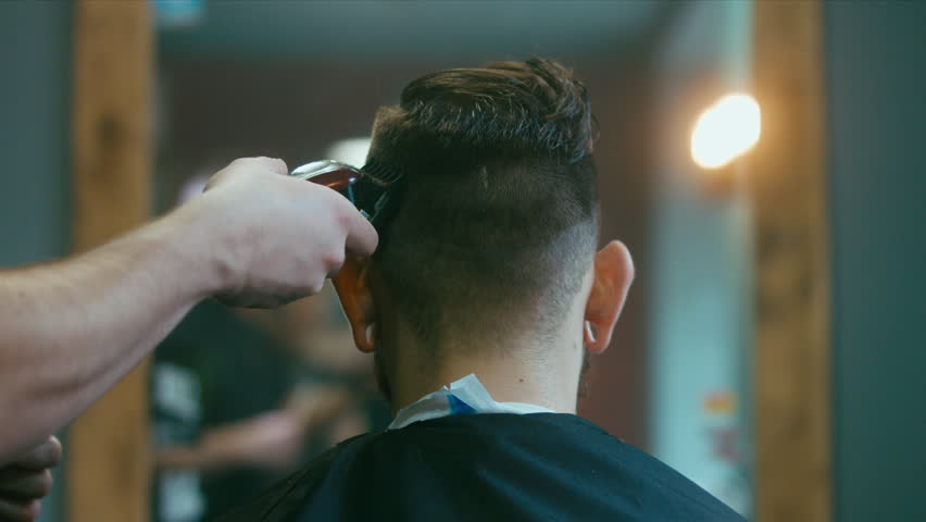 4K CINEMAGRAPH - Young handsome Caucasian man getting a haircut in a modern barber shop. Seamless loop. 4K UHD Raw edited footage
