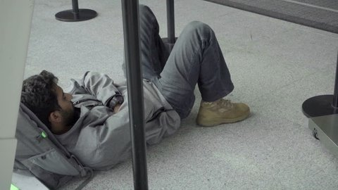 NEW YORK - SEPTEMBER 29, 2016: Traveler Sleeping On Airport Floor Passenger Asleep Waiting Flight in NY. JFK is a major international airport located in Queens.