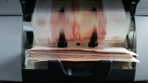 Cash money banknote counting machine counting 5000 ruble bills. Close-up.
