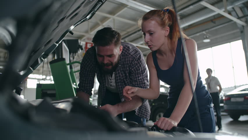 Man and woman in mechanic uniform checking details under car hood and fixing the breakdown #21259942