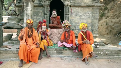 KATHMANDU, NEPAL - APRIL 7, 2016: Group of Sadhus sending greetings to tourist at Pashupatinath Temple. In Hindu religion the Sadhus are holy men.