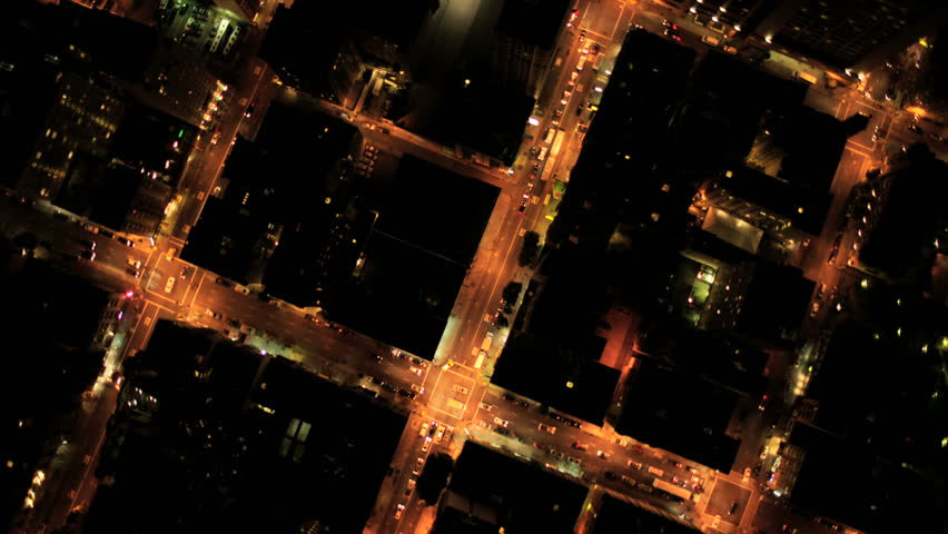 Aerial vertical view at night of city traffic illuminated by city streets and skyscrapers, North America, USA