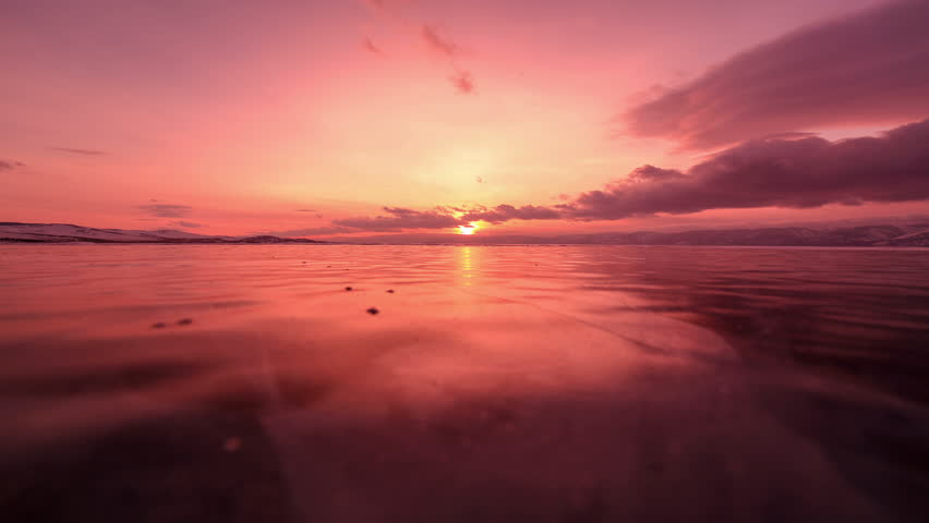 4K. Sunset in the icy Lake Baikal in the red colors, Irkutsk region, Russia. Ultra HD, 4096x2304