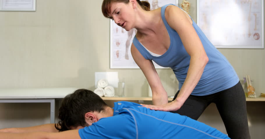 Female physiotherapist assisting man with exercise ball in the clinic 4k