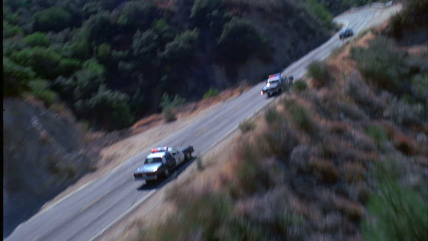 day Aerial remote area two police cars chasing blue silver car mountain road Car chase
