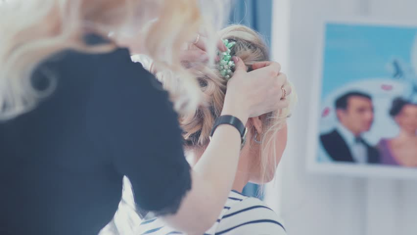 Wedding styling. Wedding hairstyle. Final touches to the hairstyle. Accessory for wedding hairstyles. Decoration in hair. Blonde woman helps the bride to choose the barrette in her hair.   Shutterstock HD Video #21337072