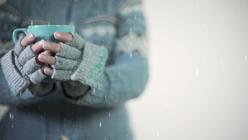 Woman warming up hands with light blue woolen gloves, blue pullover and a woolen cup of coffee or tea while it's snowing. Snowflakes. | Shutterstock HD Video #21343942