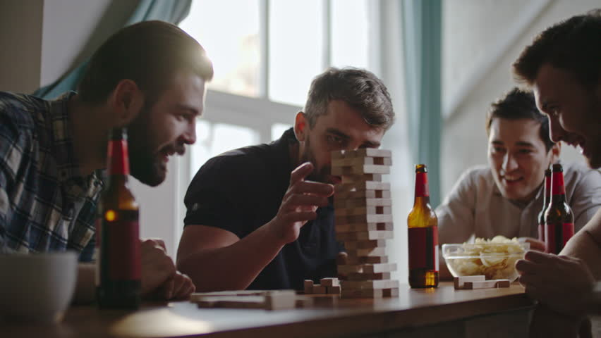 Guys laughing and high-fiving each other as their friend making jenga tower fall by accident