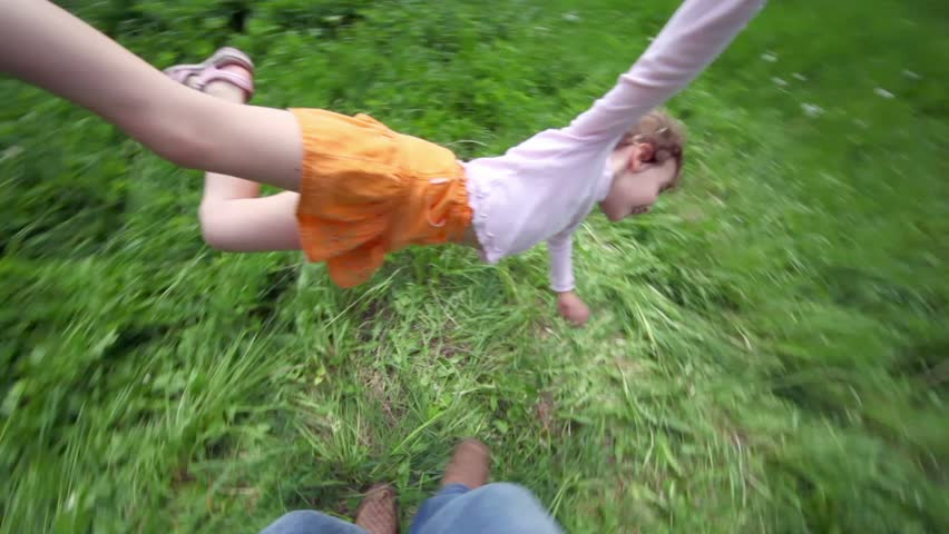 Hand holds little girl by her hand and leg, she flies above grass at background of forest | Shutterstock HD Video #2135372
