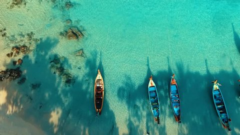 Aerial: Long tail boats on beautiful beach.