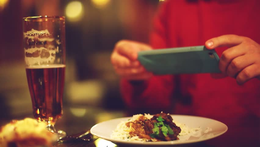 Close up of hands with smartphone taking a pic of food for social network site at bar or pub. 1920x1080