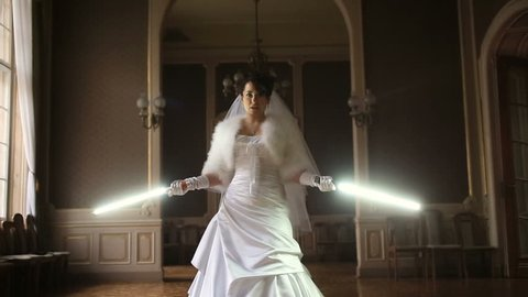 Funny pretty bride playing jedi with lightsaber