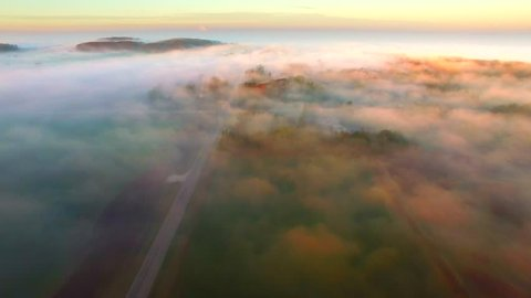 Surreal Autumn flight over foggy landscape at first light.